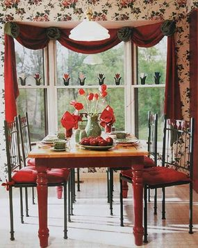 © Solid red curtains span this breakfast nook bay in the form of valance swags held in place by large rosettes in a contrasting fabric.