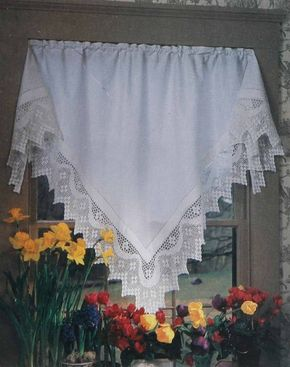 © Imitating a tablecloth at the window, this triangular valance in crisp white linen is trimmed with a deep edge of crocheted lace.