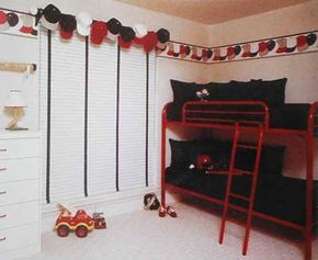 © A one-of-a-kind baseball-cap valance over a long window matches the room's black, white, and red palette. Privacy is guaranteed by white blinds trimmed in black tape.
