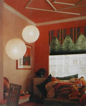 © A paper pleated shade is topped by a jester valance in an irregular-striped print repeated on the accent pillows.
