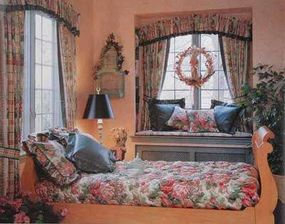 © Wide, patterned hanging shades tied back with matching ribbon form the perfect complement to the floral print on this rooms furniture and pillows.