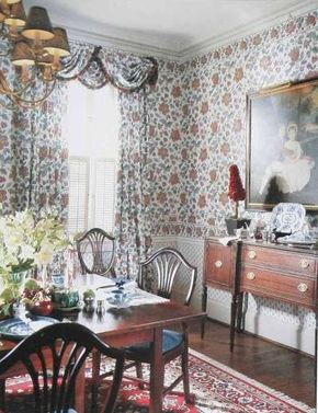 In traditional style, the classic floral print is continued from the walls to the window. The only break in the flow is the fringe-edged scalloped valance.