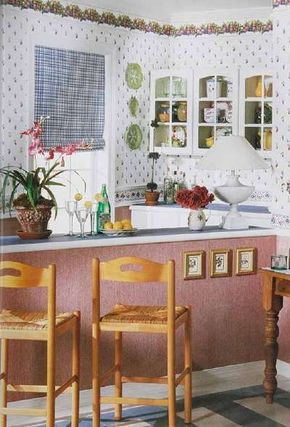A small-scale blue and white plaid fabric window shade relates to this kitchen's fruit-motif wall covering in terms of scale.
