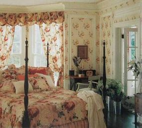 Floral draperies with a cloud valance continue the garden theme on this bedroom's walls and bed linens, announcing the space's gracious country English style.