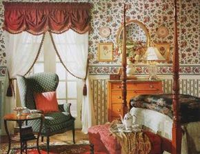 A theater-curtain valance provides a striking counterpart to sheer panels trimmed in burgundy fringe and tasseled cording tiebacks.