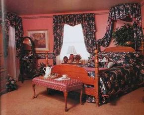 A canopy bed is created by repeating the window treatment's valance with banded edging over matching bishop's-sleeve draperies on the ceiling and walls.