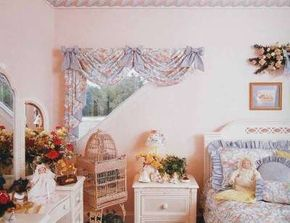 Chintz hangs at valance length and is tied with bows to take a soft double-swag shape. The floral chintz fabric shows its blue lining as it cascades on the side.