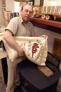 Woody Keeney pours wood pellets from a standard 40 pound bag into a wood pellet burning stove. 