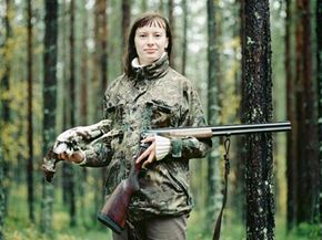 Young woman with riffle holding a dead willow ptarmigan in her hand in the forest in Lapland, Finland