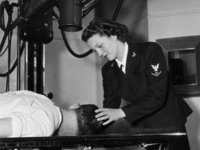 U.S. Navy pharmacist's mate Dorothy Abbott adjusts a patient's head, preparing to take X-rays of his skull.