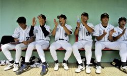 Members of China's Beijing Tigers baseball team cheer on a teammate in 2003.
