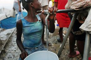 Residents of a camp for Haitians displaced from the Jan.12, 2010, earthquake fill jugs with clean water in Port au Prince, Haiti.