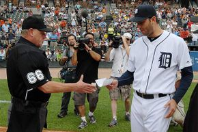 Major League umpire Jim Joyce receives the lineup card from Detroit Tigers pitcher Armando Galarraga before the start of a game against the Cleveland Indians; earlier, Joyce apologized to Galarraga for the bad call which cost him a perfect game.