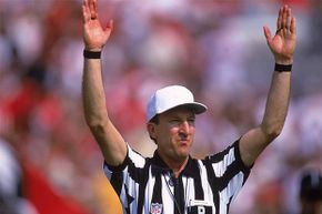 """Referee Phil Luckett signals a score during a game between the Minnesota Vikings and the Tampa Bay Buccaneers in 2000. Back in 1998, he heard the Pittsburgh Steelers co-captain call """"heads"""" on a pre-game coin toss. Everyone else heard """"tails."""""""