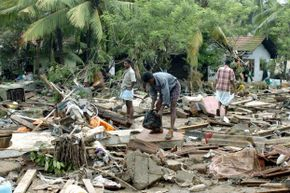 Sri Lankan residents pick through debris from a massive tidal wave.