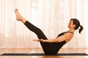 A woman performing boat pose.