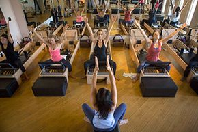 Women work out during a master Pilates class using reformers, a piece of Pilates equipment that provides support and resistance.