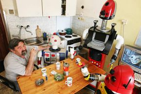 The Czech inventor Stanley Povoda, nicknamed 'The Robot Man' poses with his iron robot family at his home in Prague, Czech Republic.