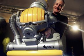 Inventor James Dyson demonstrates his latest hoovering invention on March 14, 2005 in London. The vacuum cleaner replaces the traditional four wheels with one ball to guide it across the floor giving it increased maneuverability.