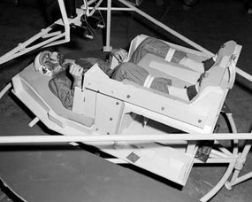 An astronaut sits in a spacecraft simulator in the zero-gravity position.