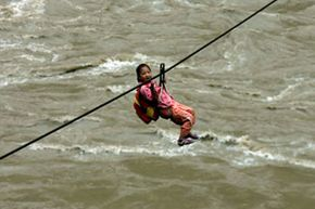 Chinese third-grader Yu Lina crosses the Nujiang River to get to class at the Center Primary School of Maji Township on a zip line on Sept. 15, 2007. Around half of the school's students use the lines to get to and from school due to the distance of bridges across the river.