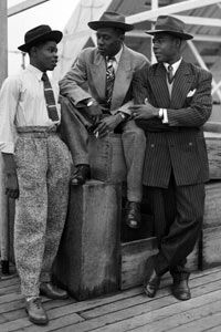 Three Jamaican immigrants (left to right) John Hazel, a 21-year-old boxer, 32-year-old Harold Wilmot, and John Richards, a 22-year-old carpenter, dressed in zoot suits and trilby hats.