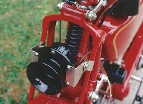 Girder-style forks and a compressed coil provided nominal suspension travel.