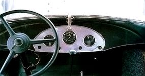 Common to this era, the first-series 1933 Graham Blue Streak Series 57 Eight instrument cluster was placed in the middle of the dashboard. The handle at the top opens the windshield for ventilation.