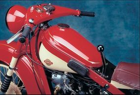 Frame rails surrounded the fuel tank, the gear lever was centrally mounted, and the handlebars were pressed steel.