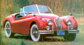 A lush wooded setting is perfect for this XK-140 roadster, though this is an American model and scene. See more classic car pictures.
