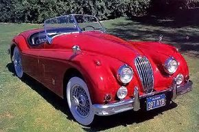 """""""Wide stripe"""" grille, chrome hood strip, and heftier bumpers were the main outward changes on the XK-140 of 1954-1957."""