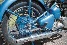 An oil tank beneath the seat helps identify this Triumph as housing its engine and transmission in separate cases. Triangular box above foot peg is a tool compartment.