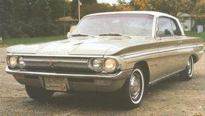 The 1962 Oldsmobile F-85 Jetfire's sidedraft single-barrel carburetor and turbo body were tucked neatly under a hood trimmed by twin windsplits.