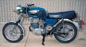 Long forks, a small front wheel, and a boxy fuel tank gave the TS250 an awkward stance.