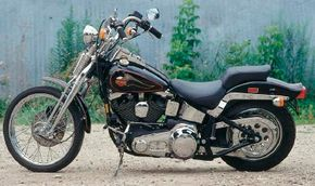 The Softail Springer's rear suspension incorporated a triangulated swingarm that extended a pair of coil-over shocks mounted beneath the bike.