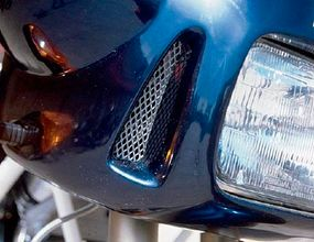 Headlights and taillights are flanked by decorative grilles.