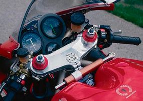 The copper-colored cylinder behind the fork brace is a steering stabilizer.