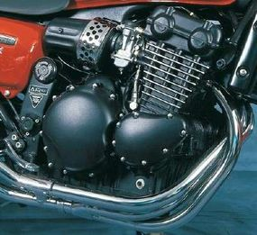 The twin-cam, water-cooled triple had three exhaust pipes. They flowed into two mufflers, with the two outside pipes joining under the engine.