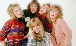 """A 1980s stock photo. The caption reads: """"Five friends smiling, wearing sweaters and eyeglasses."""""""