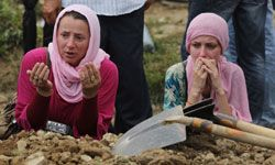 Two Muslim women pray at a grave during a mass funeral in Potocari, Bosnia, in July 2011.