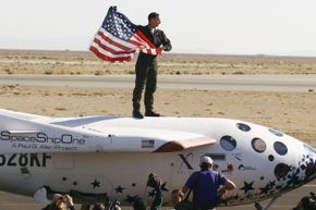 Pilot Brian Binnie holds an American flag after SpaceShipOne won the $10 million dollar Ansari X Prize. Awards like this can reinforce commercial space development.