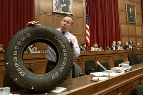Congressman Fred Upton (R-MI) displays a Firestone tire with tread separation that came off a friend's Ford Explorer on June 19, 2001, during an oversight and investigations hearing of the Commerce, Trade, and Consumer Protection subcommittee.