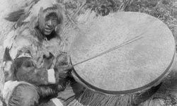 In this photograph circa 1929, this Eskimo man is holding a drum made of walrus skin or bladder.