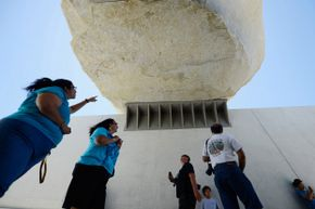 """Visitors stand beneath the """"Levitated Mass."""""""
