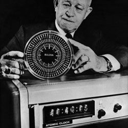 General Omar Bradley (1893 - 1981), who commanded the 12th U.S. Army during the D-Day landings, shows a rock crystal clock produced by his company as well as an atomic clock.