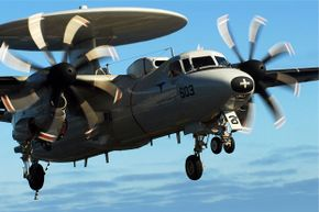 You can clearly see the landing gear on this E-2C Hawkeye as it approaches the flight deck of USS John C. Stennis.