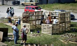 Volunteers work on the kitchen of a wood-pallet home in a Miami, Fla., shanty town.