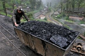 A miner pushes a cart loaded with coal at Bagou village, in China's southwest Sichuan province, on April 13, 2006.