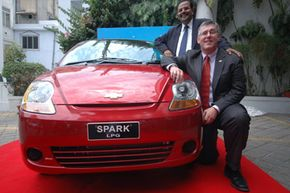 General Motors India President Karl Sylm (front), and Vice President of Corporate Affairs P. Balendran pose with the newly launched liquefied petroleum gas version of the compact Chevrolet Spark in Ahmadabad, India, on June 22, 2009.