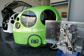 """A compressed-air engine is shown on display next to """"AirPod"""" cars at the MDI (Motor Development International) head offices in Carros, near Nice, France, on Jan. 30, 2009."""